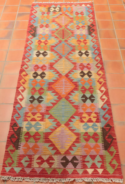 A mixture of red, orange, heather, green, gold, cream, blue and dark brown have been used in this kilim runner.