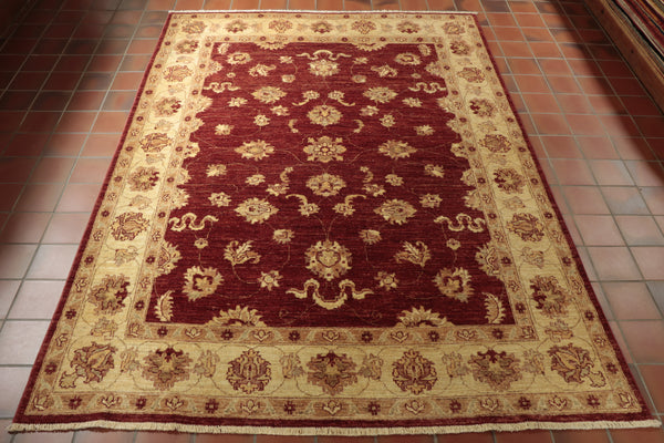 This finely hand-knotted Afghan Ziegler is a true classic, from its burgundy centre-ground and edging to its combination of beige and gold features throughout.