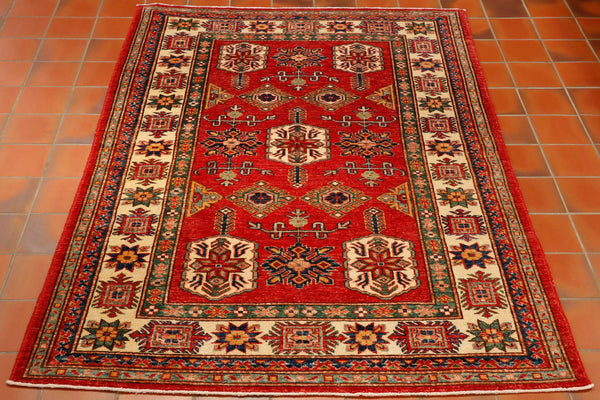 A traditional Caucasian design rug that has been hand knotted in north west Afghanistan. The background colour is a tomato red with the main border having a cream background colour. Other colours in the pattern and minor borders are green, both pale and dark blue and peach. An overall light coloured practical rug that will brighten your room.