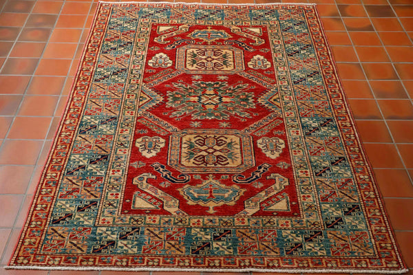 Excellent quality fine Afghan Kazak rug approximately 6ft x 4ft. The more tightly knotted the rug is the better definition in the pattern and this rug has a very sharp geometric design. Every step of work on this rug is done by hand from the sheering of the sheep, the carding and spinning of the wool, the dyeing, the all important weaving and then the washing and many different finishing processes. The colouring is tomato red with soft gold, green and differing shades of blue.