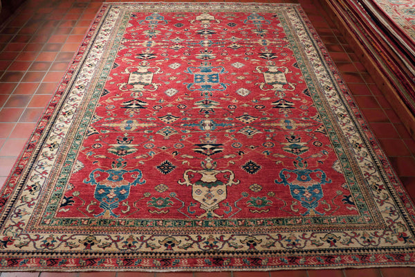 This is a beautiful example of a fine Afghan Kazak hand knotted using wool in an usual Caucasian design.  The background colour is a terracotta/red with the main border being in cream and an inner border in a lovely shade of green. There is very little dark blue in this piece, instead they have used a lighter blue.