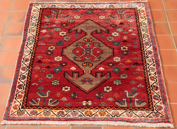 This is a characterful rug woven by the women of the Qashqai tribe in southern Iran. The sit and spin the wool by hand and use natural products that are around then for the dyes. the backgrou colour is a soft re with a camel coloured geometric medallion in the middle and a cream border. As well as flowers scattered on the background there are 12 stylised peacocks.