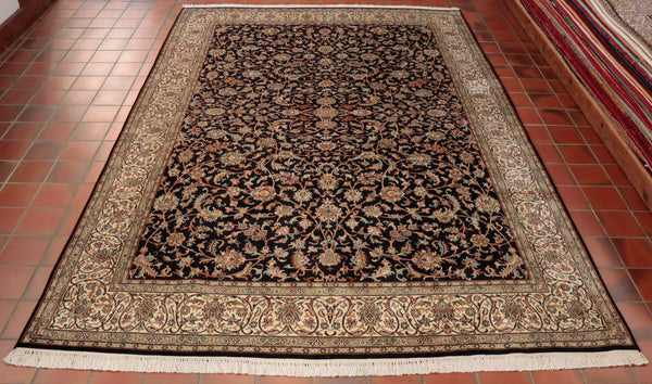 This Kashmir carpet has an intricate Persian floral design. It has been hand knotted in Kashmir using silk for the pile and cotton for the warp and weft. The background colour is a very dark navy blue and the border is ivory. Other  colours used are rust, olive green, rose pink and duck egg blue.