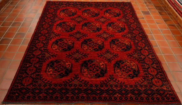 A really rich burnt orange coloured Afghan Ersari rug hand knotted in north west Afghanistan using vegetable dyed hand spun wool. The design is one of the most traditional from that part of the world and is often referred to as the elephants foot pattern. The other colours used in the design are a very dark navy blue and little touches of a bright green to highlight the design.