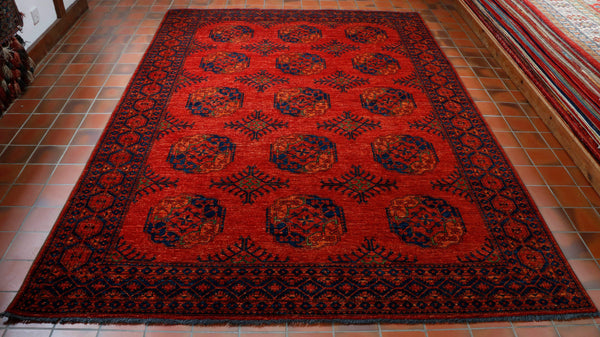 Wow, what a wonderful rich flame orange colouring. The design is a repeating medallion which is often referred to as the elephants foot. This is in a dark blue and softer orange tone with tiny touches of bright green entwined in the pattern. The carpet has a border which is the flame colour with4 the dark blue. The rug is made from 100% wool pile, warp and weft and is extremely practical and hard wearing.