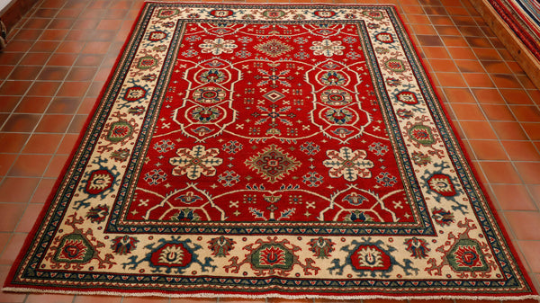 This is a hand knotted Afghan Kazak. It is made from wool woven on to a cotton foundation. The quality is good but it is what we term a commercial quality, not quite as finely knotted as most of our rugs and made with machine spun wool. This is obviously reflected in the price as it is relatively inexpensive. The background cour to the central panel is a vibrant red with a cream border. Other colours used in the design are soft green and a mid blue.