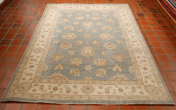 An Afghan Ziegler rug is made from hand knotted wool on a cotton foundation. The pattern is a gentle flowing open floral design. The over all colouring is very muted with a soft pale blue background, a cream border and fawn and very pale terracotta in the design.