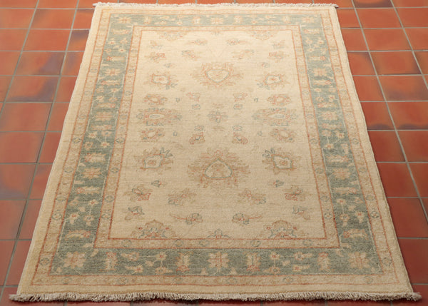 This is a hand knotted Afghan Ziegler in very pale gentle colours. Made from Hand spun Karakul wool, the background is a warm cream colour and the border a soft blue/green shade. There are traces of a soft terracotta used as highlights in the subtle floral design. This is the sort of rug that you could put in your room and it would look as if it had always been there.