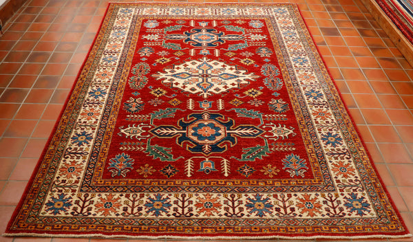 This is a fine quality Afghan Kazak rug made from a wool pile on to a cotton foundation. The finer the quality the crisper the design and the detail is very sharp on this rug. The colours used are a rich red for the background and a cream border with a large cream diamond medallion in the centre. Other colours used are light and dark blue, touches of salmon pink, gold and a sea green.
