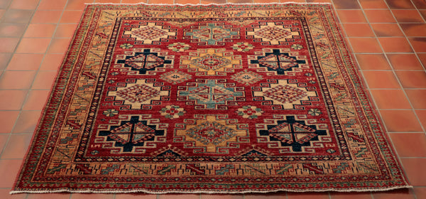 A beautiful hand made Afghan Kazak with a golden glow. The background colour is a soft tomato red with a gold border and cream and blues of different shades in the geometric diamond motifs. It is made from vegetable dyed Afghan wool from the Karakul sheep that roam the mountainous terrain in Afghanistan.
