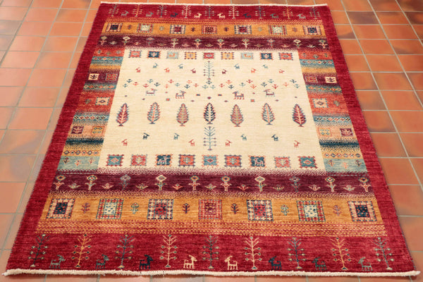 A fabulous Afghan Loribaft rug hand made from northwest Afghanistan. The Loribaft are made using all the traditional methods that have been passed down from generation to generation but they are made using strong blocks of colour and stylised trees and little geometric goats. There is a large central block of cream in the centre of this rug scattered with the goats and trees. The outer border is a plain brick red and other colours used are old gold, pale blue, terracotta and a burgundy shade.