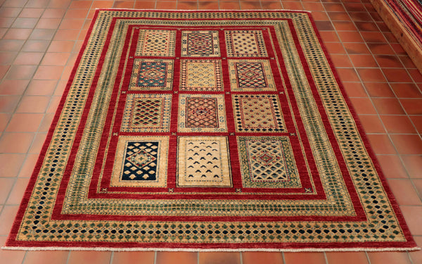 A fine quality hand knotted wool rug from northwest Afghanistan. It is an unusual design in that the centre panel is made up of 12 individual rugs. The main colourings are a rich red, pale gold, soft green, cream and touches of light and dark blue.