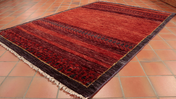 the rug is a rich red with possibly and Aubergine colour