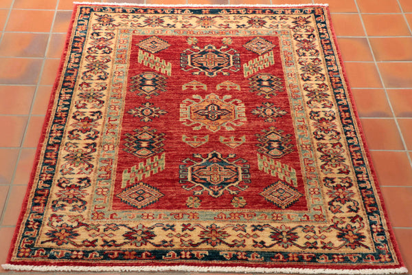 This rug is made from wool pile woven on to a cotton warp and weft. The background colour is a tomato red and it has a honey cream border. Other colours used include light and dark blue and a tangerine shade. The pattern is a classic geometric Caucasian design. The quality is very good and therefore this rug can be used anywhere within the home.