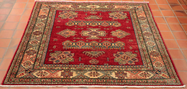 A very striking rug that would be ideal for a hall with a small round table on it. Squares are always difficult to come by as the weaver could earn more money if they carry on and weave a rectangular shape. This piece has a lovely rich red background with cream border, different shades of blue, green and gold in the design. The geometric pattern originates from the Caucasus.