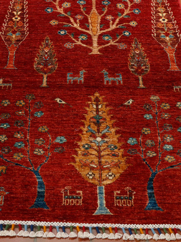 Vivid red background with different types of trees and quirky goats woven in to the pattern.