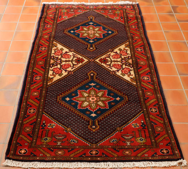 Hand knotted in the town of Rudbar in north west Iran. The design is a mix of large geometric diamond in the middle of the rug and roses in the side sections. The rug is made from wool pile knotted on to a cotton foundation. The size is ideal for a hall way or in front of the fire. The colouring is mainly a brick red with  dark blue and old gold. The pink roses are on a cream background.