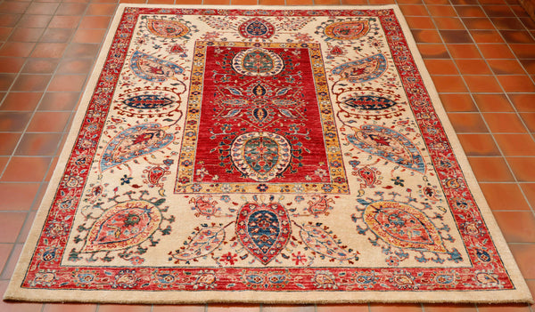A beautiful Afghan Aryana rug hand knotted using a design from Central Asia. Very often this design can be found in exquisite silk embroideries made by hand in Uzbekistan. There is a panel in the centre of the rug in a soft almost pinkish red with a narrow border in gold . The background to the wide main border is a cream colour and other shades used are Wedgwood blue, dark green , peach and deep blue. The construction is wool on to a cotton foundation.