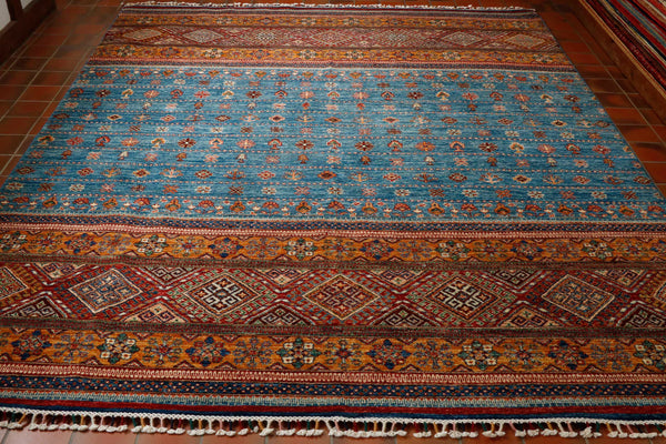 A beautiful hand knotted carpet from north western Afghanistan. It is made from vegetable dyed hand spun wool woven on to a cotton foundation. There are elements of the carpet that are very traditional with a section top and bottom in a traditional intricate geometric diamond design, however the middle section in the light blue colour is much more simple which gives it a modern twist.