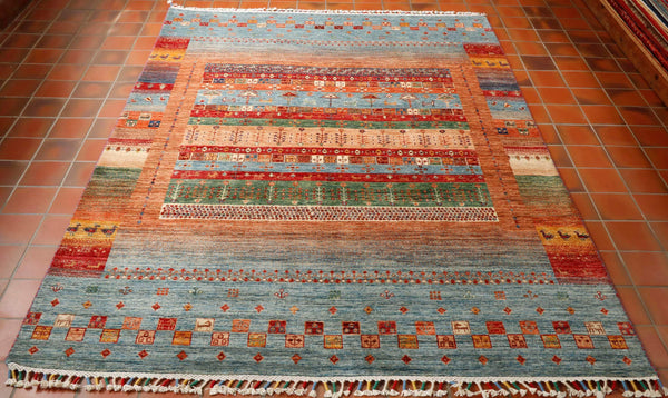 This Afghan Kharjeen is hand made using a wool pile woven on to a cotton warp and weft. Although this has been made using traditional methods that have been passed down through generations, the design and colouring is more modern. The pattern is made up of bands of colour in differing widths from pale blue and soft peach to brick red and green with a little dark blue and saffron. There are even some tiny stylised birds and animals woven in to the rug.