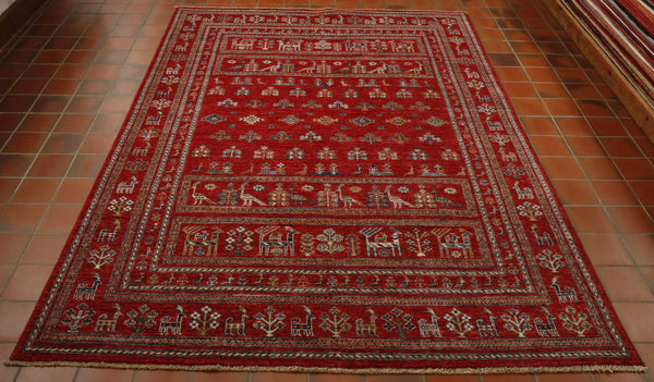 This hand knotted Kharjeen has been hand knotted in north west Afghanistan using a wool pile woven on to a cotton warp and weft. Whilst the weaving and dying has been done using traditional methods the design of this piece is more modern. The border and centre of this rug is covered in little stylised peacocks, goats and trees.