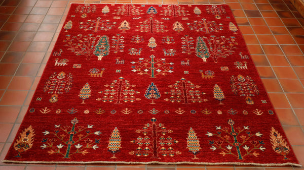 This Afghan Aryana is very much a picture rug. Made from wool and vegetable dyes in north west Afghanistan this rug is covered in different types of trees and stylised animals and peacocks. The main colour is a strong brick red and other colours used are a sea green, peach, burgundy, blue and cream. A fabulous rug with lots of character and interest.