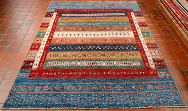 This is a striking example of one of the many contemporary designs that are being produced in northwest Afghanistan.  There is a wonderful mix of colours that are portrayed in wide bands. These colours include denim blue, brick red, sandy gold, dark blue, tangerine, cream, deep green and coffee colour. To give the rug some extra character the weaver has put some little stylised animals in the side borders. Made from wool hand knotted on to cotton this piece will fit beautifully in to a modern lifestyle.