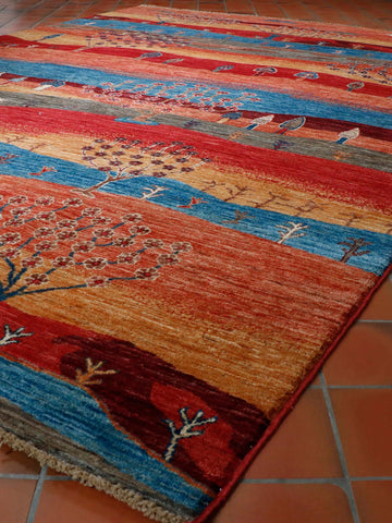 A very striking hand knotted Afghan Kharjeen rug. A modern style with a kaleidoscope of coloured bands with many different types of trees scattered throughout the carpet. The colours include burgundy, gold, sky blue, sage green, peach and brick red. A functional piece of art for a contemporary room.
