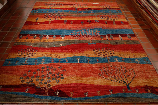 A striking Afghan rug with a colourful modern design. Essentially the design is replicating the different terrains in different colours with many different types of trees woven in the the bands of colour. The colours include brick red, sky blue, peach, gold, sage green and touches of cream.