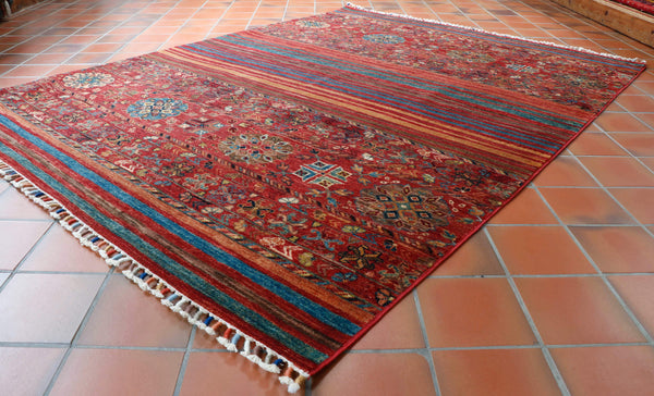 The reich red is produced from the root of the Madder plant. Often the roots are boiled to extract the natural red colouring that is the foundation of this and many other hand made vegetable dyed Oriental rugs and carpets