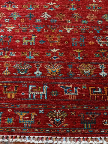 This Samarkand rug design is quite different from most. The theme is more loosely based on old Caucasian design, it also is perhaps a little less formal, the pattern of stylised animals and birds in bands across the rug makes it vey interesting. It certainly has the typical bright colours of Samarkand based upon a rich red with the gentle blues and golds throughout the design .