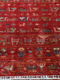 a vibrant hand made Afghan rug, it has a wonderful attention to the flora and fauna of the region.