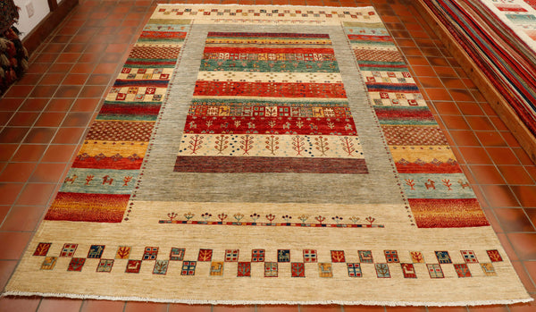 A hand knotted modern Afghan Loribaft rug with a wool pile and a short cotton fringe. The over all feeling of the colouring is a lovely light rug in stripe design. The colours used are cream, soft grey, red, terracotta, light and dark blue, gold and sea green. There are even some stylised quirky animals woven in to the design.