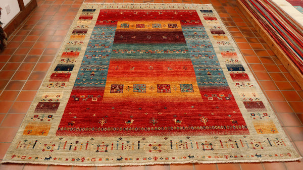 Wonderful, vibrant colours of brick red, flame orange, pale blue, dark blue,  saffron, burgundy and sea green surrounded by a border of oatmeal. This piece has been made with a very modern feel to the design whilst still using all the traditional methods ie vegetable dying and hand spun wool. There are even some random tiny stylised goats and camels woven in to the design.