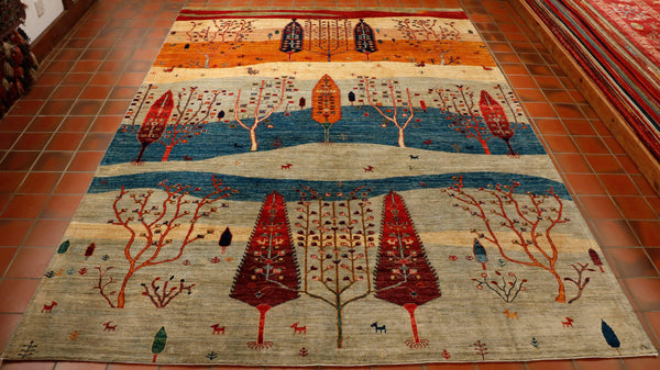 Stylised tree design Afghan rug in colourings of pale grey, mid blue, old gold, cream and brick red