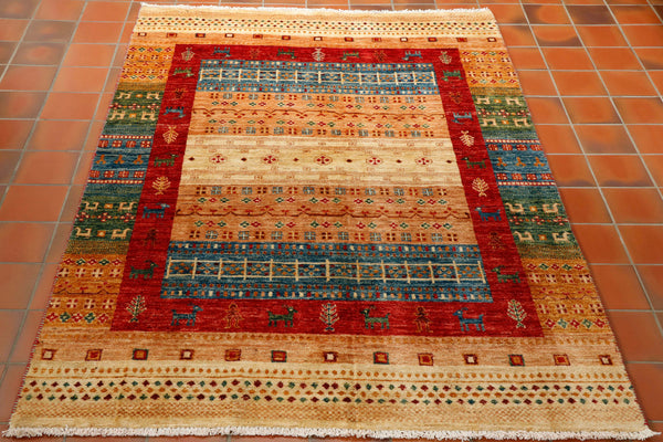 Lovely light coloured Afghan modern design Loribaft with wide bands of colour in buttermilk, pale blue, soft peach and dark green with an inner border of tomato red, which contains some little stylised goats. Hand knotted using vegetable dyed hand spun wool this rug will give colour and character to any room.