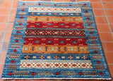 Modern Afghan rug with blue outer border and wide stripes of cream, old gold and brick red