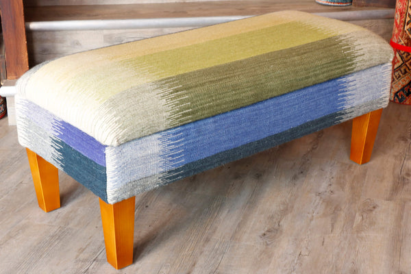 Modern looking ottoman covered in Indian kilim in shades of gold, green and blue.