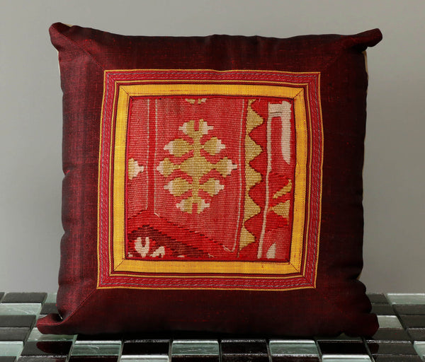 Central panel is from an old anatolian kilim in soft red and gold. this is framed by a plain burgundy Uzbeck silk border