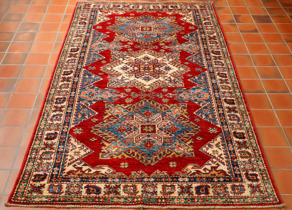 This striking bold geometric design rug has been made in north west Afghanistan using hand spun vegetable dyed wool. It has 3 large star shaped medallions running down through the centre of the rug, two blue and a cream one in the middle. The shades of colour are a tomato red for the background, light blue and dark blue, gold and touches of salmon pink.