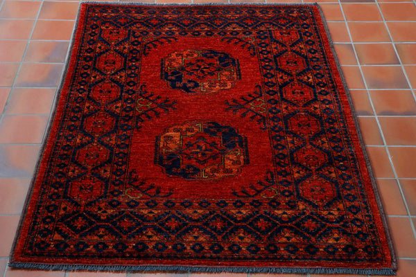 A classic design hand knotted wool Afghan rug in a rich flame orange colour with dark blue in the gulf (medallions) and in the border pattern. This is a very tough hard wearing, practical rug that will be suitable for anywhere in the home.