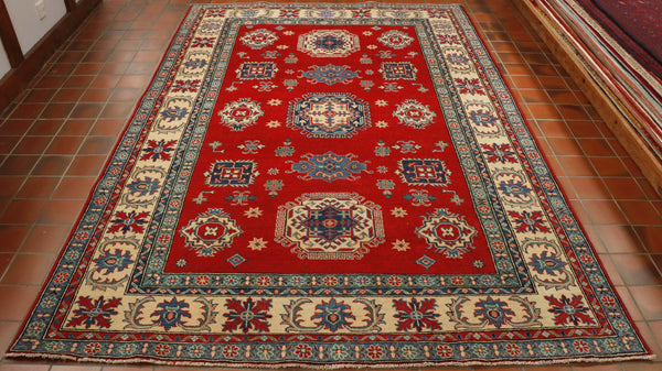 The bright vibrant colours of red, cream and two different shades of blue can be seen across the design of this rug.  The central section accommodates a mix of stylized flowers and medallions.  Whilst the borders, of which there are five of varying widths house further smaller flowers, leaves and geometric designs.