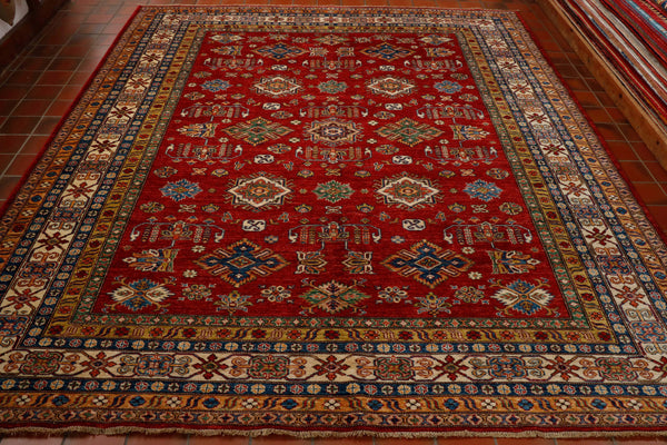 Hand made, practical, hard wearing, vibrant red background Afghan Kazak  with seven borders in cream, gold, green, dark blue and tangerine. Design in the main body of the carpet is a smaller than usual geometric all over pattern. It is made from vegetable dyed hand spun wool on to a cotton foundation. It has a short cotton fringe.