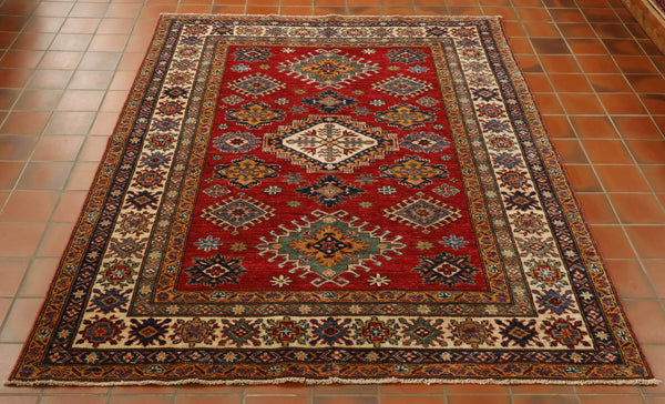 This geometric Afghan Kazak rug is 6'7 x 4'11 in size. The cream of the inner border really stands out in this particular Afghan piece. Hand made in north west Afghanistan using the wool from the Karakul sheep, this piece offers colour and practicality. The  background colour is a rich red with old gold, navy blue and deep green in the geometric design.
