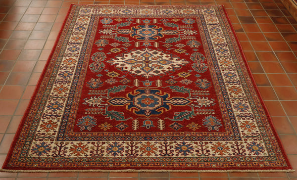 This Kazak has a lovely light cream border contrasted with the bold red centre ground. Other colours used are light and dark blue, sea green and peach. The rug has been hand knotted in north west Afghanistan using a traditional geometric Caucasian design.