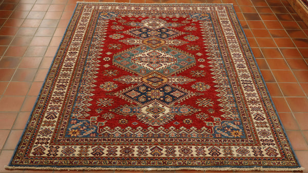 Although this rug has been hand knotted in Afghanistan, the design originates from the Caucasus. This rug has a strong brick red background with a cream border. The design is very bold and geometric with colourings of green, blue, gold and cream