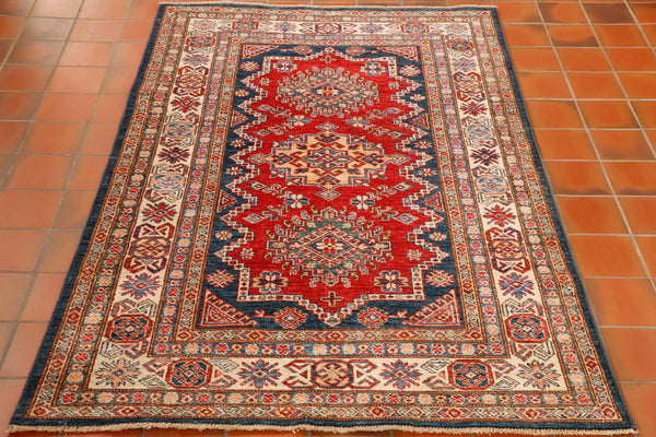 A hand made wool Afghan Kazak rug with a geometric design with red background, ivory border and dark blue outer border. Made using a traditional Caucasian design this rug will brighten any room and offer colour and character.