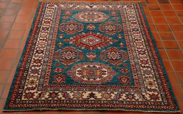 This Afghan Kazak rug is a most unusual colour. The background is a deep teal colour and the main border is cream. The other colours used in the geometric pattern are red, dark blue, gold and touches salmon pink. The rug is made from a wool pile woven on to a cotton foundation.