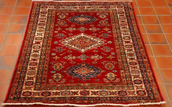 This is a classic example of an Afghan Kazak rug. It has been hand knotted in north west Afghanistan using wool from the Karakul sheep that wander the mountainous terrain. The design is actually a typical Caucasian geometric pattern. The colours used are predominantly rich red for the background with cream, green, tangerine and dark blue.