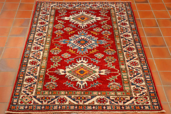A colourful hand knotted Afghan Kazak rug with a bold geometric design. Strong tomato red background with blue, green, tangerine and ivory colours. This is a practical hard wearing rug suitable for any location in the home.